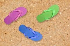 Scarpe variopinte della spiaggia sopra giallo sabbia Fotografia Stock