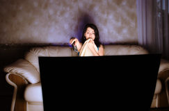 Scarred beautiful girl watching TV. On a couch stock photo