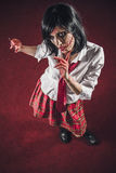 Scarred horror zombie schoolgirl. Scary undead woman holding a razor blade, her face in deep scars stock photos