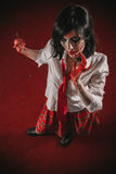 Scarred horror zombie schoolgirl. Scary undead woman holding a razor blade, her face in deep scars royalty free stock photos