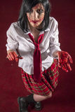 Scarred horror zombie schoolgirl. Scary undead woman holding a razor blade, her face in deep scars stock photography