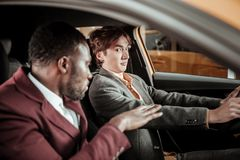 Young dark-eyed man feeling scarred while learning driving. Scarred man. Young dark-eyed men feeling a little bit scarred while learning driving stock image