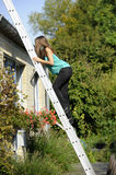 Scarred woman on a ladder. Scared woman on a ladder . outdoors stock photography