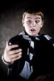 Scarry teenager looking at his mobile phone royalty free stock photography