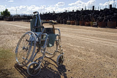 Scars at Sundown. An empty lonely wheelchair in a junkyard stock images