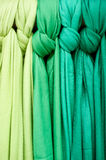 Scarves hanging on display. Selection of scarves on display at a London market of differing shades of green from light to dark stock photography
