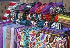 Scarves och stack häftklammermatare i en gatamarknad, Uzbekistan Arkivbild