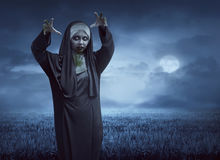 Scary asian nun on a black cape standing Royalty Free Stock Photography