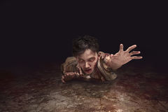 Scary asian zombie man crawling. From the dark room Royalty Free Stock Image