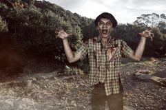 Scary asian zombie man with wounded face and claw hand. In an abandoned place royalty free stock photo