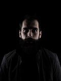 Scary bearded man staring at camera. High contrast low key dark shadow portrait isolated over black background Stock Photos
