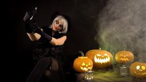 Scary beautiful girl witch celebrates halloween, makes selfie with funny glowing burning pumpkins in smoke. Woman with stock video