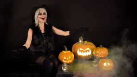 Scary beautiful girl witch laughs, taunts, gloats, celebrates halloween with funny glowing burning pumpkins in smoke stock footage