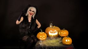 Scary beautiful girl witch laughs, taunts, gloats, celebrates halloween with funny glowing burning pumpkins in smoke stock video footage
