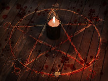 Scary black candle in pentagram circle with bloody drops. Scary Halloween collage with black candle, blood drops and pentagram circle on wooden table. Dark magic Stock Image