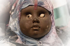 Scary black doll face. Very old and broken stock photo