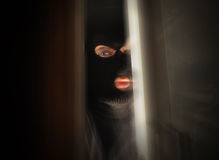 Scary Burglar Breaking In House. A man with a black mask is breaking into a home and the focus is in his eye. Use it for a security or danger concept Stock Image