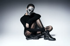 Scary calm woman sitting on the floor. In studio Stock Image