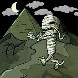 Scary cartoon Egyptian mummy in front of pyramids.  Stock Image