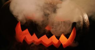 Scary carved halloween pumpkin in hot burning hell fire flames. The big helloween pumpkin has a mad face with glowing. Carved Halloween pumpkin lights and smoke stock footage
