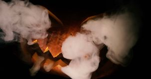 Scary carved halloween pumpkin in hot burning hell fire flames. The big helloween pumpkin has a mad face with glowing. Carved Halloween pumpkin lights and smoke stock video footage