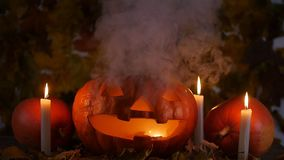 Scary carved pumpkin on Halloween in hot fire and smoke stock video