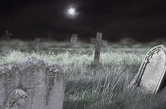 Scary cemetery at night. Composition of a moonlit cemetery with fog and old crosses. Ideal for Halloween Stock Photos