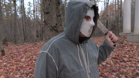 Scary character in scary Halloween mask and machete in the park. In autumn day stock video