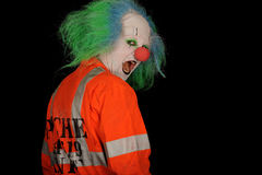 Scary clown. Half body portrait of scary clown wearing green wig and fluorescent jacket looking over shoulder, black background