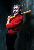 The scary clown and baseball-bat on dack background. Halloween concept Royalty Free Stock Photography