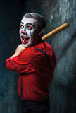 The scary clown and baseball-bat on dack background. Halloween concept. The scary clown and baseball-bat on dack. Halloween concept of horror and murderer