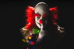 Scary clown on a dark background. High contrast image of a scary clown on a black background royalty free stock photos