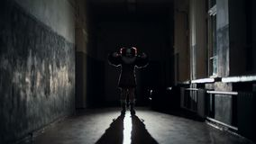 Scary clown in a dark corridor at night scares a man in slow motion