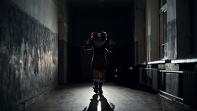 Scary clown in a dark hallway at night goes to a man in slow motion. Frightening clown with colorful makeup in a carnival costume moves his hands against the stock video
