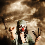 Scary clown doctor throwing knives outdoors Stock Photos