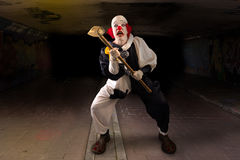 Scary clown with a hammer. Standing in a tunnel Royalty Free Stock Photography