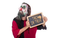 Scary Clown holding a sign, text Trick or treat, isolated on whi Stock Photos