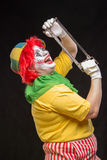 Scary clown joker with a smile and red hair with a saw on a blac Royalty Free Stock Images