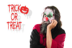 Scary clown looking to Text Trick or Treat, isolated on White, C Royalty Free Stock Photos