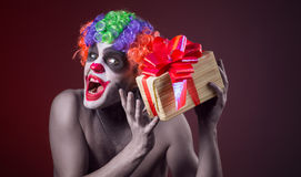 Scary clown makeup and with a terrible gift Stock Image
