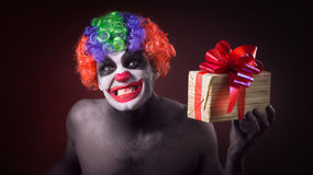 Scary clown makeup and with a terrible gift Royalty Free Stock Photo