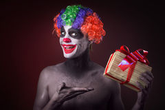 Scary clown makeup and with a terrible gift Stock Photography