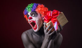 Scary clown makeup and with a terrible gift Royalty Free Stock Photos