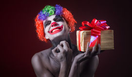 Scary clown makeup and with a terrible gift Royalty Free Stock Image