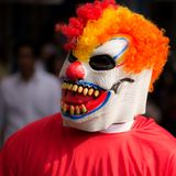 Scary Clown. Man with a scary clown mask walks in street