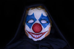 Scary clown mask on a dark background Stock Photography