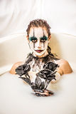 Scary clown milk bath. Milk bath for a scary clown. Sensual beautiful female model in a bath tub of milk for Halloween. Creepy clown face paint with black gloves Royalty Free Stock Images