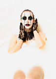 Scary clown milk bath. Milk bath for a scary clown. Sensual beautiful female model in a bath tub of milk for Halloween. Creepy clown face paint with black gloves Royalty Free Stock Photos