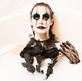 Scary clown milk bath. Milk bath for a scary clown. Sensual beautiful female model in a bath tub of milk for Halloween. Creepy clown face paint with black gloves Stock Image