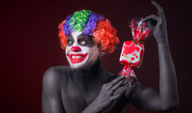 Scary clown with spooky makeup and more candy Royalty Free Stock Images